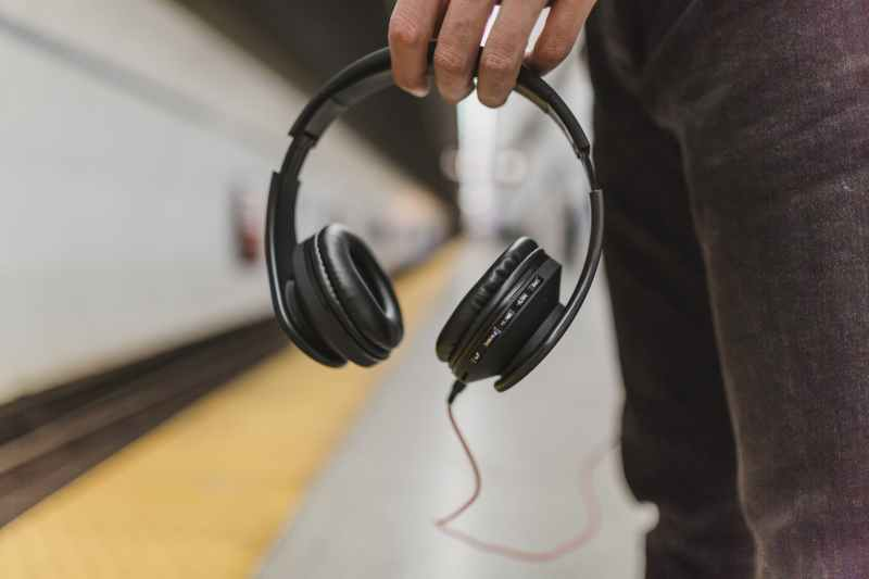 shallow focus photography of person holding headphones